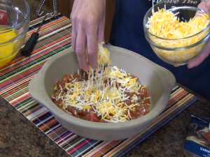 Kristi sprinkles shredded cheese over salsa.