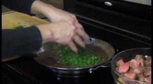 Jess adds thyme to gravy.