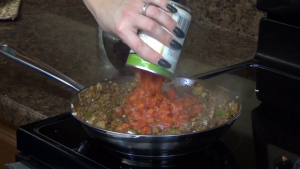 Jess adds tomatoes to ground beef mixture.