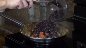 Jess adds beans to the ground beef and vegetable mixture.