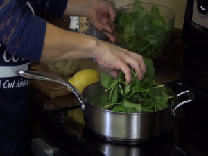 Jess adds spinach to a saucepan.