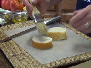 Kristi brushes bread.