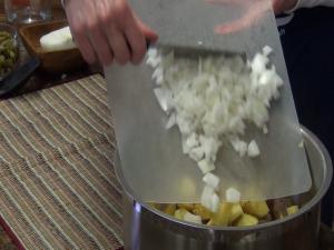 Kristi places onion into pan.