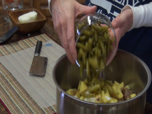 Kristi adds green beans to pot.