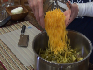 Kristi adds shredded cheese to pot.