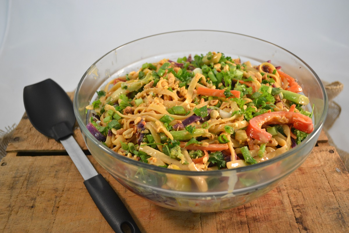 A bowl of vibrant Thai Rainbow Noodles with Peanut Sauce beside a Rada Non-Scratch Spoon.