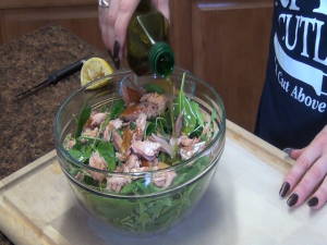 Jess adds olive oil to a salad.
