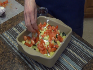 Kristi adds tomatoes to dip.