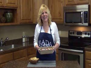 Kristi poses with her Rada Rectangular Baker filled with Greek dip.