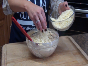 Jess adds shredded cheese to chicken mix.