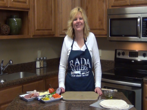 Kristi stands with hot deli wrap ingredients.