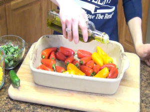 Jess pours olive oil over peppers placed in a Rada Rectangular Baker.