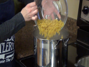 Jess adds noodles to boiling water.