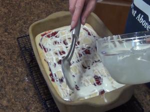 Kristi uses the Rada Ice Cream Scoop to ladle icing on cherry bars.