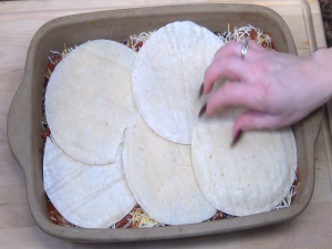 Tortillas are added to pan.