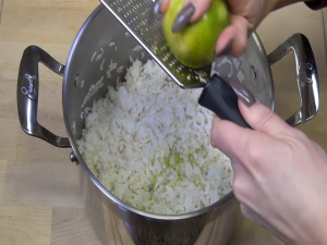 A lime is zested over rice.