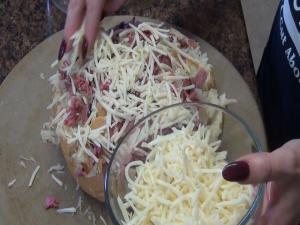 Jeff sprinkles cheese on top of bread.