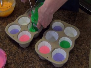 Kristi pours batter into muffin pans.