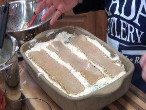 Jess adds lasagna noodles to pan.