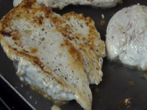 Chicken breast cooks in the skillet.