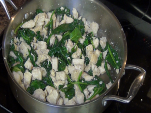 Spinach cooks down in pan.