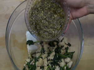 Pesto is added to chicken and spinach mixture.