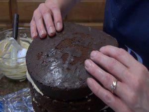 Kristi layers on a cake.