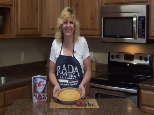 Kristi poses with a completed impossible buttermilk pie.