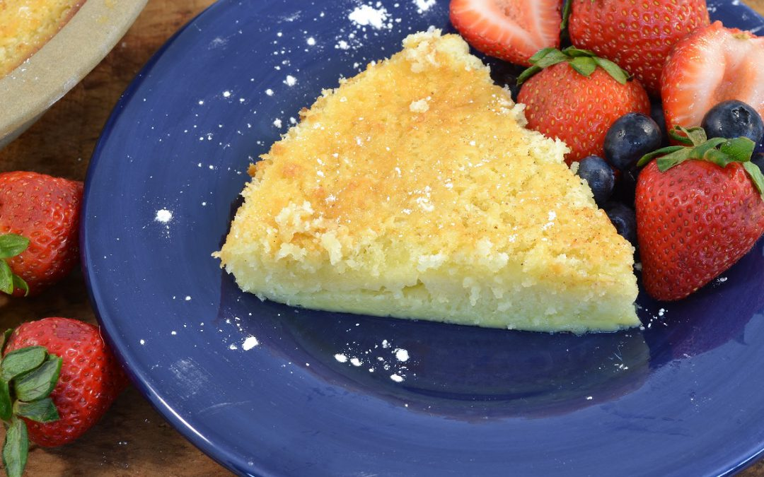 A slice of impossible buttermilk pie with some fresh strawberries.