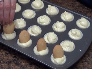 Jess adds vanilla wafer cookies to tin.