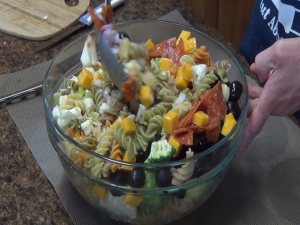 Kristi stirs pasta salad with a Rada Cook's Spoon.