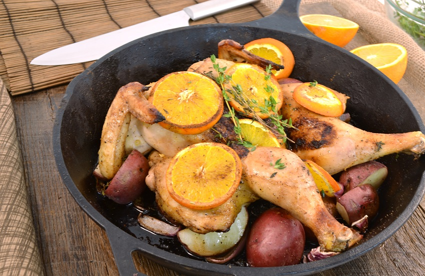 A skillet with beautiful butterflied roasted chicken and vegetables.