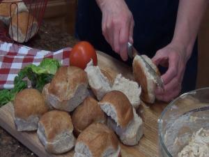 """Kristi cuts rolls with the Rada 6"""" Bread Knife."""