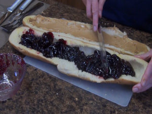 Kristi applies grape jelly to French bread.