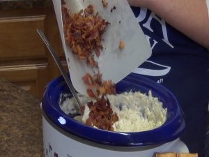 Kristi adds bacon to slow cooker.