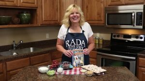 Kristi poses with chicken salad ingredients and Rada recipe book.