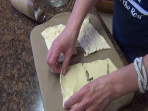Kristi presses out crescent dough.