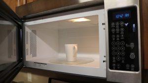 Kristi prepares microwave.