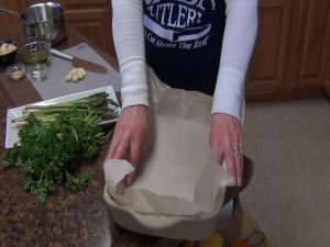 Kristi lines the Rada Rectangular Baker with parchment paper.