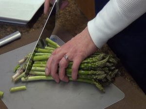 Kristi removes asparagus tips with Rada French Chef knife.