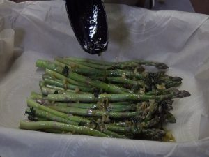 Kristi adds garlic to asparagus.