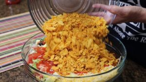 Kristi adds chips to taco salad.