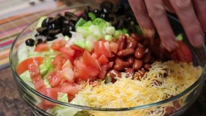 Kristi adds vegetables to taco salad bowl.