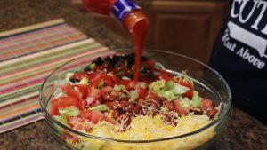 Kristi adds sauce to taco salad.