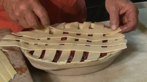 Dan adds dough lattices to pie.