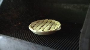 Dan places cherry pie in smoker.