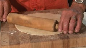 Dan uses a rolling pin to flatten pie crust dough.