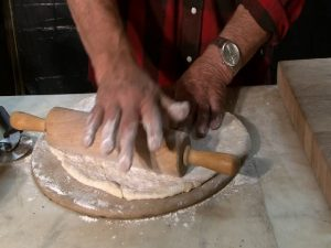 Guy Fitzgerald rolls pizza dough on a Rada Baking Stone.