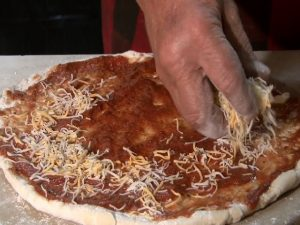 Guy Fitzgerald places cheese on a pizza crust.