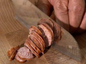 Guy slices kielbasa with a Rada French Chef knife.